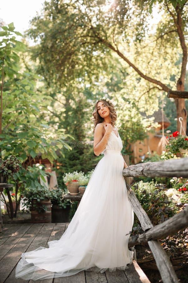 一套白色婚礼礼服的一名逗人喜爱的卷曲在她的站立回到照相机的头发的妇女与婚礼花束和花圈本质上 库存照片