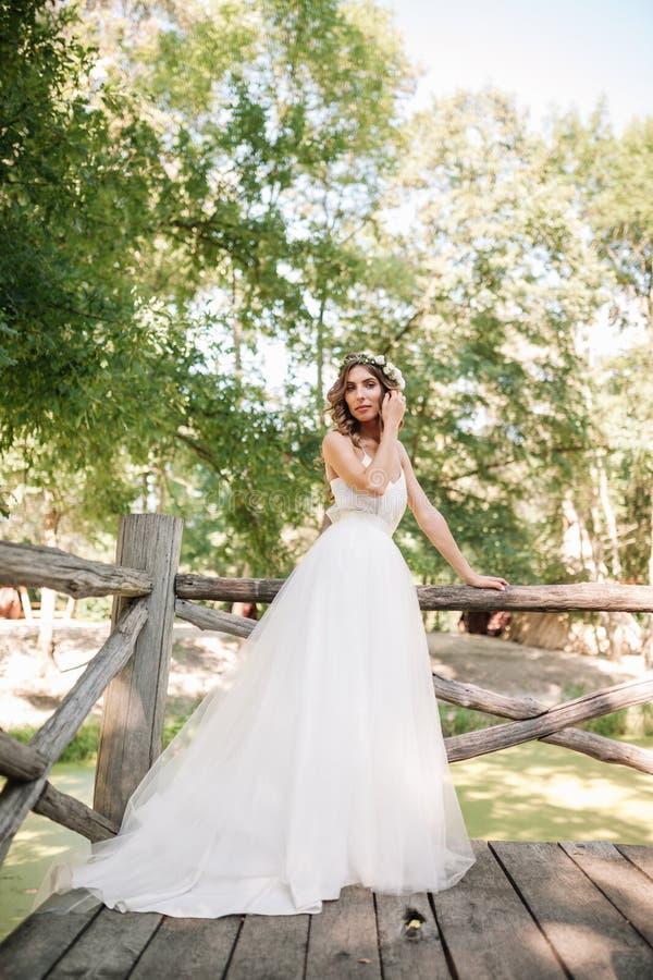 一套白色婚礼礼服的一名逗人喜爱的卷曲在她的站立回到照相机的头发的妇女与婚礼花束和花圈本质上 免版税库存照片