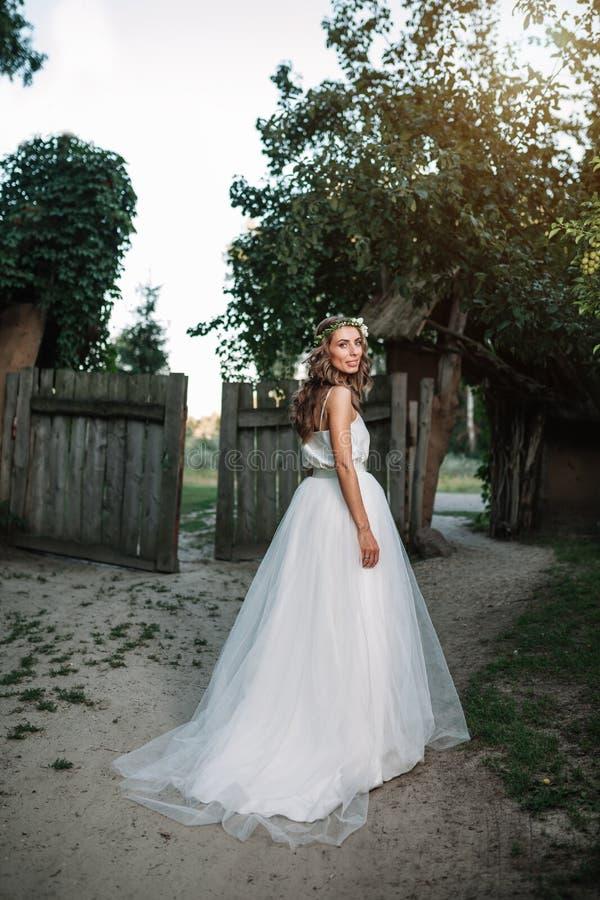一套白色婚礼礼服的一名逗人喜爱的卷曲在她的站立回到照相机的头发的妇女与婚礼花束和花圈本质上 库存图片