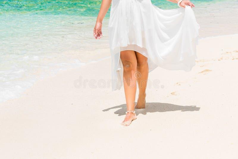 一套白色婚礼礼服的美丽的年轻新娘走在trop的 库存照片