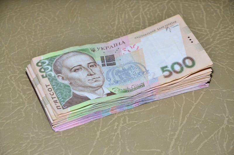 一套的特写镜头照片与500 hryvnia的面值的乌克兰金钱,说谎棕色皮革表面上 背景 免版税库存图片