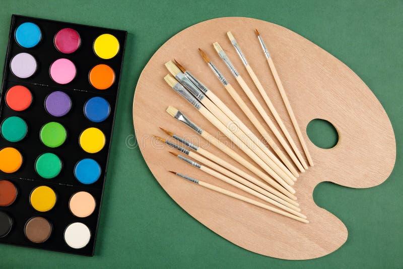 一套的顶视图水彩、木调色板和画笔的不同的类型在深绿背景的 艺术,工艺, scho 免版税图库摄影