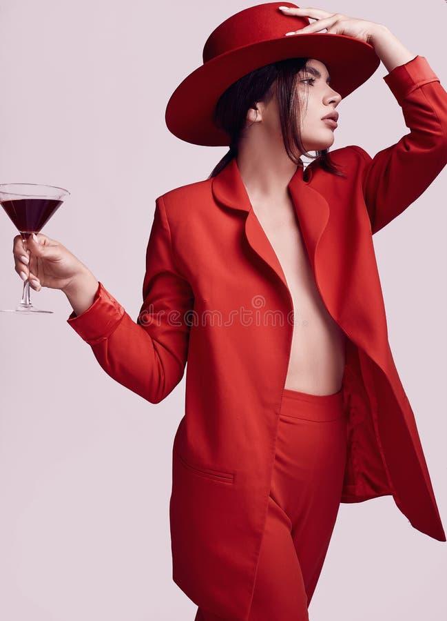一套红色时兴的衣服的典雅的美丽的有鸡尾酒的妇女和帽子 免版税库存图片
