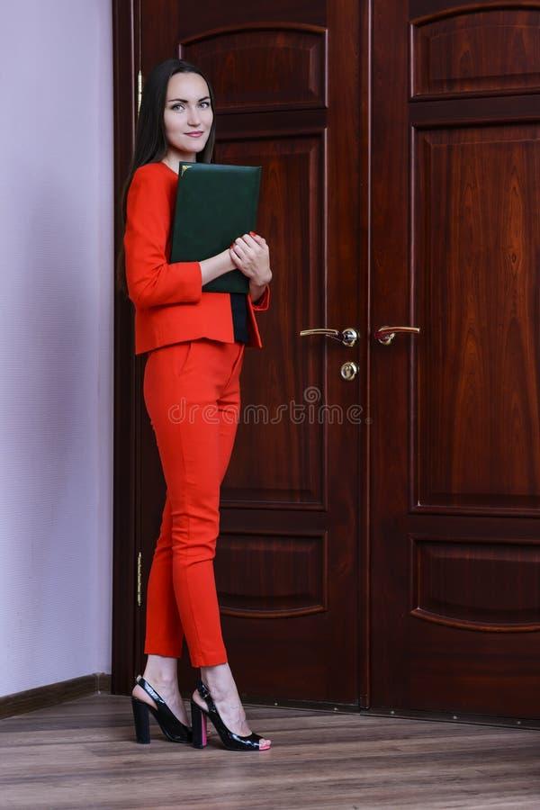 一套红色衣服的微笑的妇女与在手中敲在门的文件 图库摄影