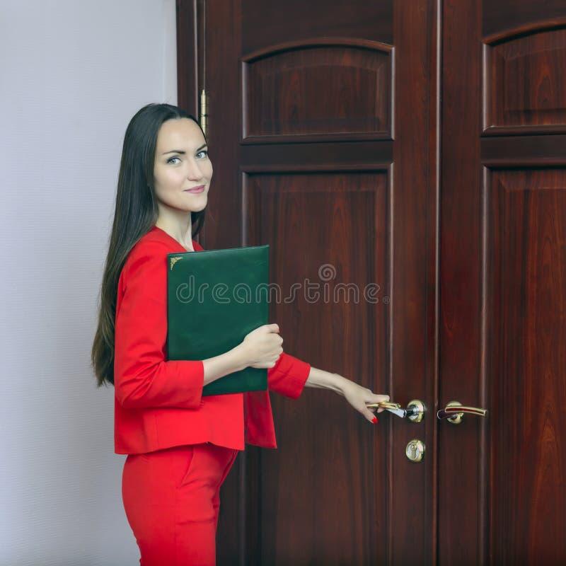 一套红色衣服的微笑的妇女与在手中敲在门的文件 库存照片