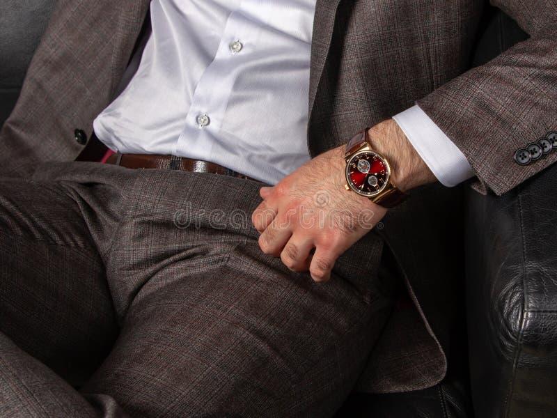 一套经典灰色衣服的一个人偶然地坐一个黑皮革沙发 免版税库存照片