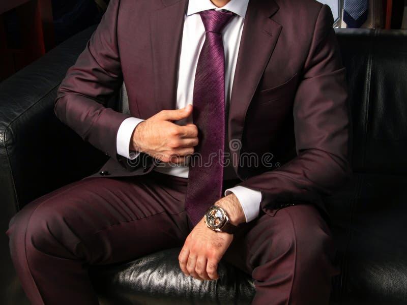 一套经典衣服的一个人坐一个黑皮革沙发,关闭  免版税库存照片