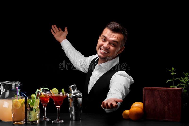 一套经典衣服的一位愉快的侍酒者在黑背景 鸡尾酒的许多五颜六色的成份在桌上 库存图片