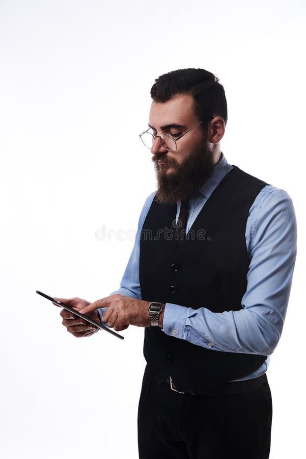 一套经典衣服的有胡子的严肃的人与片剂在手中 免版税库存照片