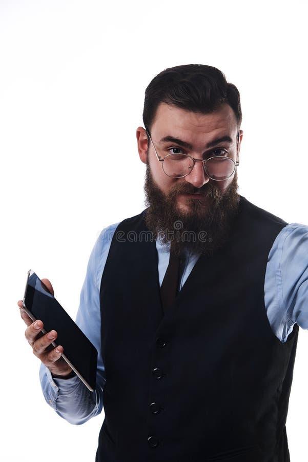一套经典衣服的有胡子的严肃的人与片剂在手中 免版税图库摄影