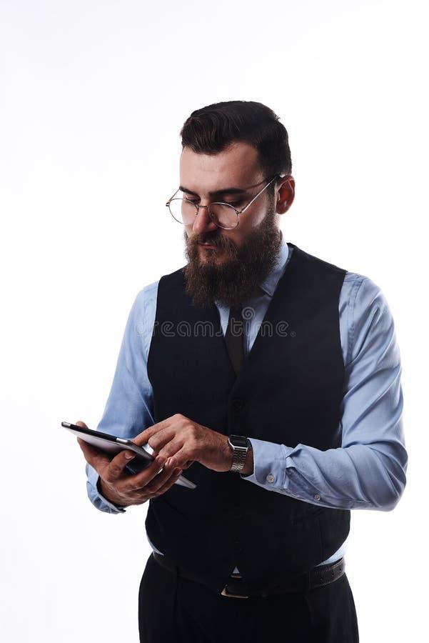 一套经典衣服的有胡子的严肃的人与片剂在手中 库存图片