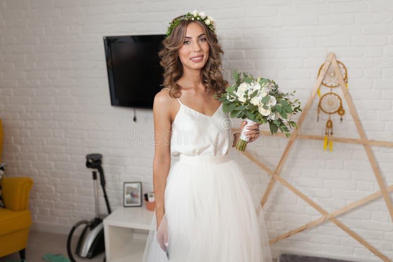 一套美丽的婚礼礼服的新娘与长的卷发在卧室站立并且看照相机 户内新娘与wh 库存照片