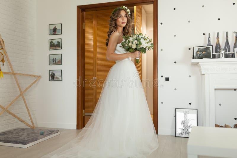 一套美丽的婚礼礼服的新娘与长的卷发在卧室站立并且看照相机 免版税库存照片