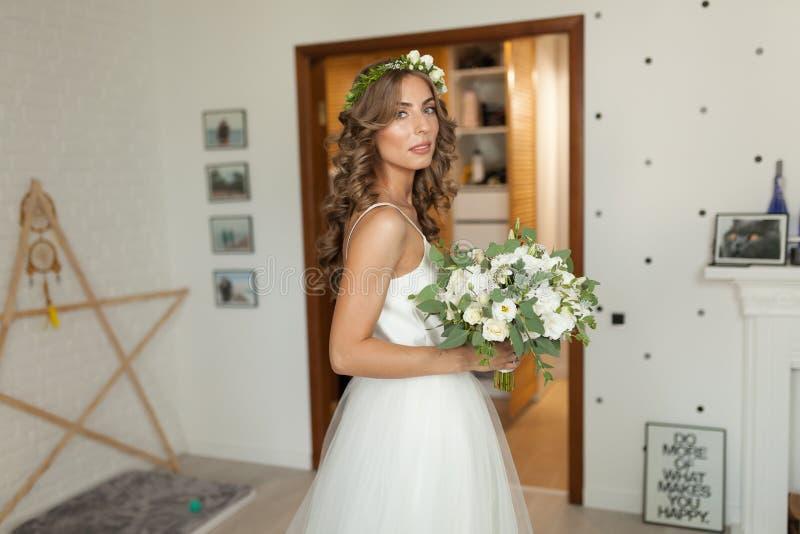一套美丽的婚礼礼服的新娘与长的卷发在卧室站立并且看照相机 图库摄影