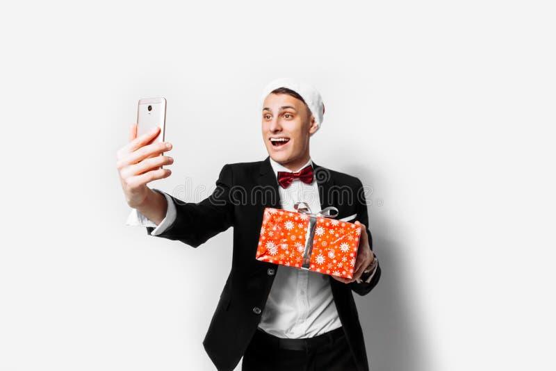 一套衣服和一个圣诞老人帽子的震惊人,在他的手- Christma上 免版税库存图片