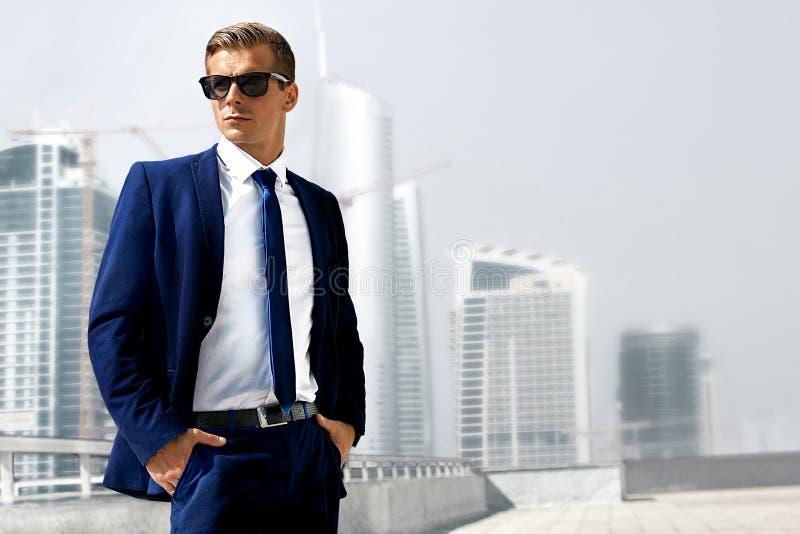 一套衣服的人反对摩天大楼背景  免版税库存图片