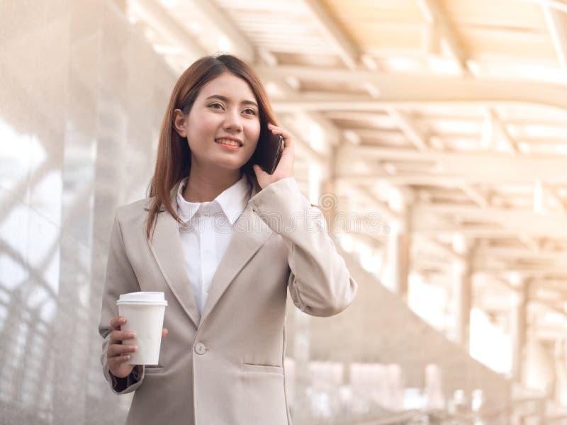 一套衣服的聪明的女商人与手机 免版税库存照片