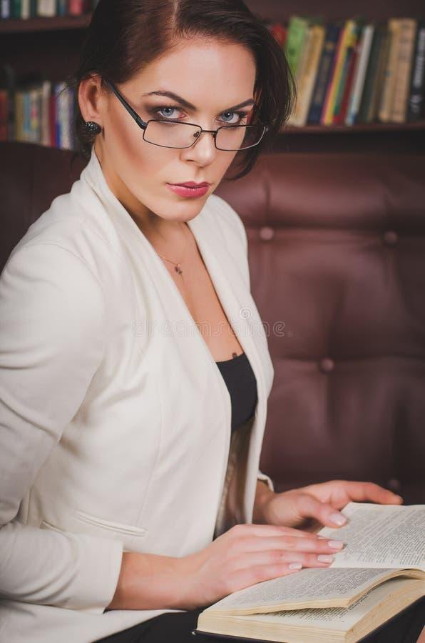 一套西装的可爱的女商人有玻璃sittin的 免版税库存照片