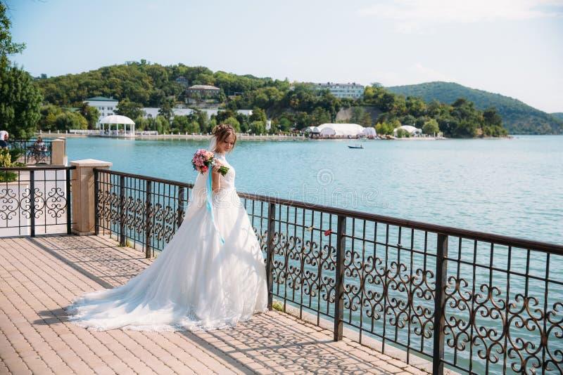一套豪华的婚礼礼服的一个女孩与与蓝色丝带的花束站立并且敬佩海湾和村庄在小山 免版税库存图片