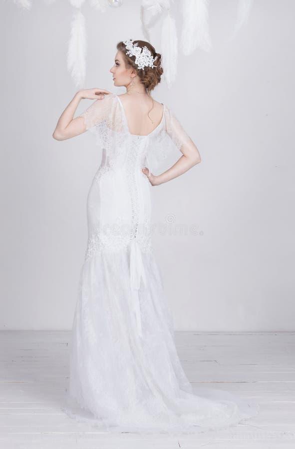 一套豪华鞋带婚礼礼服的典雅的年轻和梦想的美丽的新娘 免版税库存图片