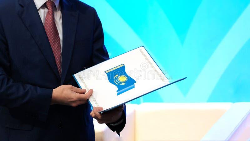 一套黑暗的衣服的一个人拿着与哈共的国旗的图象的一个被打开的文件夹 奖的概念 免版税图库摄影