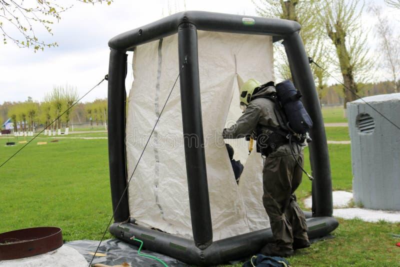 一套黑特别防火衣服的一名专业消防队员准备装配一个白色氧气帐篷对抢救人在化工 库存照片