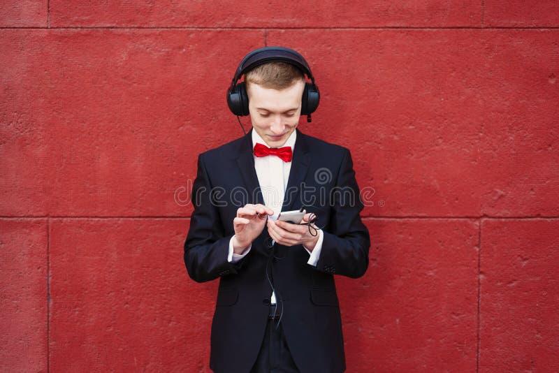 一套黑衣服、白色衬衫和一个红色蝶形领结的年轻人 大耳机的一个人听到音乐的在背景中 免版税库存照片