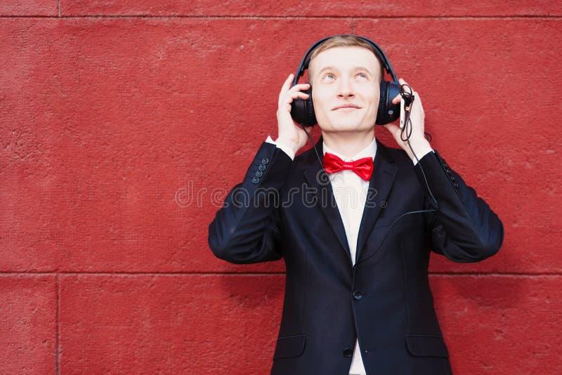 一套黑衣服、白色衬衫和一个红色蝶形领结的年轻人 大耳机的一个人听到音乐的在背景中 库存图片