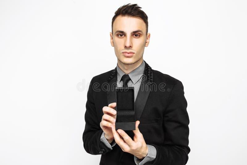 一套黑衣服的典雅的人,拿着装饰的黑盒 库存照片