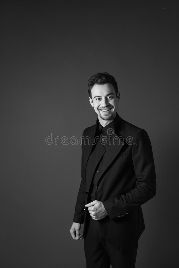 一套黑衣服的年轻英俊的人,微笑和看c 免版税库存图片