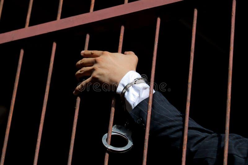 一套黑衣服的人与在他的手上的手铐在深蓝b 免版税库存照片