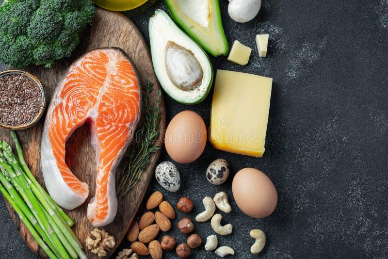 一套keto饮食的健康食品在黑暗的背景 与亚麻籽的新鲜的未加工的鲑鱼排,硬花甘蓝,鲕梨,鸡鸡蛋 免版税库存图片