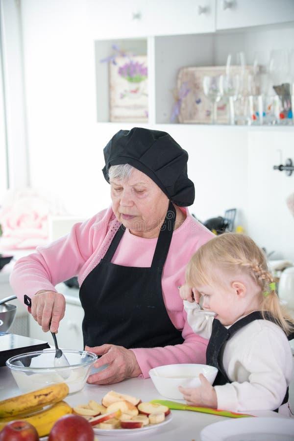 一女孩和她的祖母服务的薄煎饼与酸性稀奶油 免版税库存照片