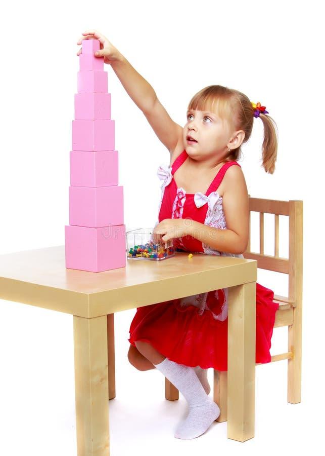 一女孩在蒙台梭利在幼儿园使用与pi 库存照片