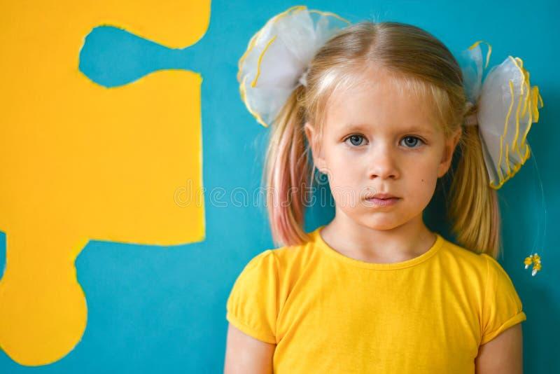 一女孩在黄色和与难题的蓝色背景的画象黄色礼服的 免版税库存照片