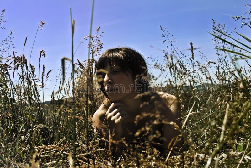 一女孩放置赤裸在草甸 免版税库存图片