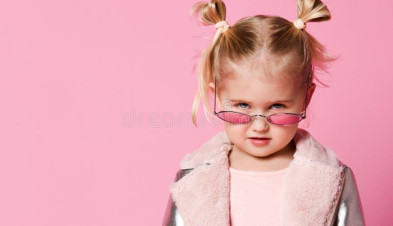 一女孩的画象夸大时髦的衣物的摆在桃红色背景和 库存照片