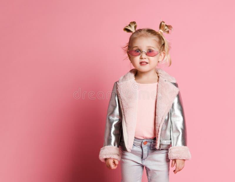 一女孩的画象夸大时髦的衣物的摆在桃红色背景和 库存图片