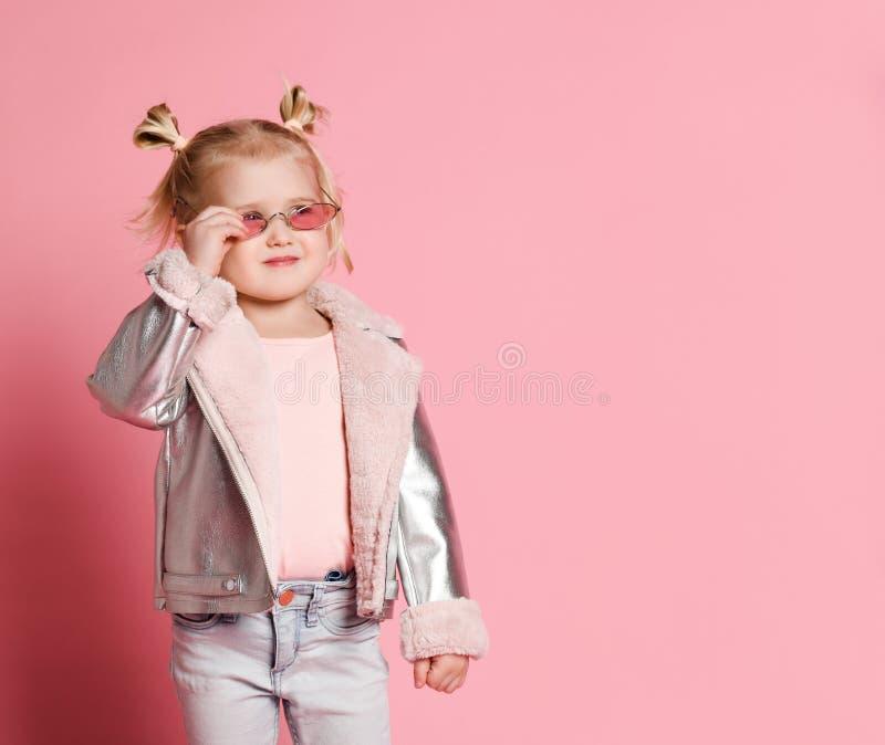 一女孩的画象夸大时髦的衣物的摆在桃红色背景和 免版税图库摄影