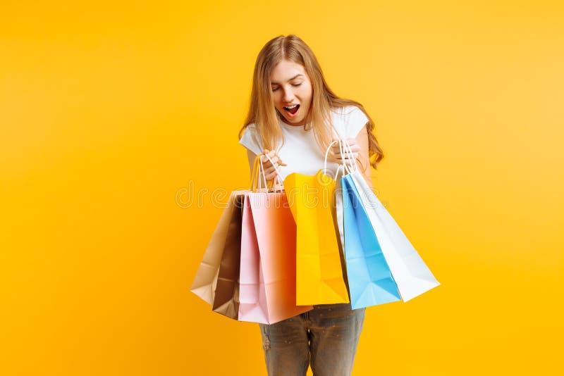 一好奇年轻女人的画象,在好购物以后,看在袋子里面,隔绝在黄色背景 免版税图库摄影