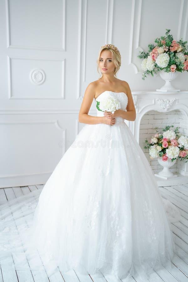 一婚纱有美好的构成的和头发的美女在一个白色演播室 免版税库存照片