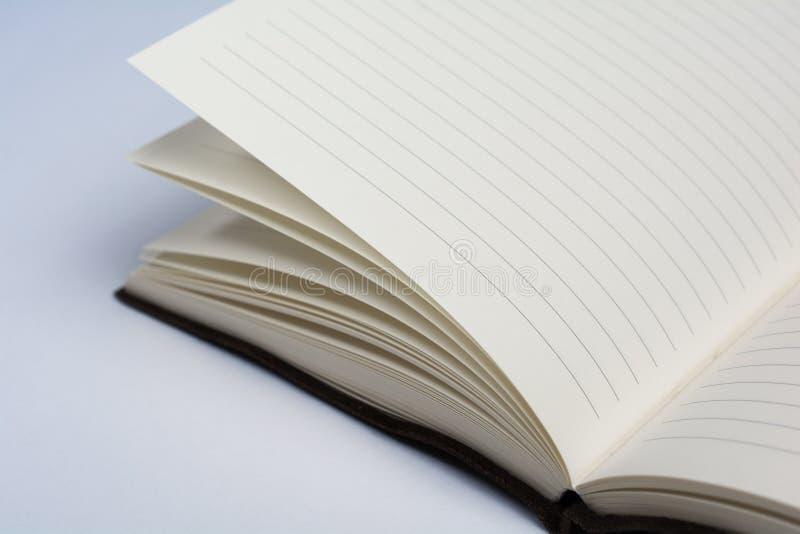 一定的皮革学报书开放在显示页的白色 免版税库存照片
