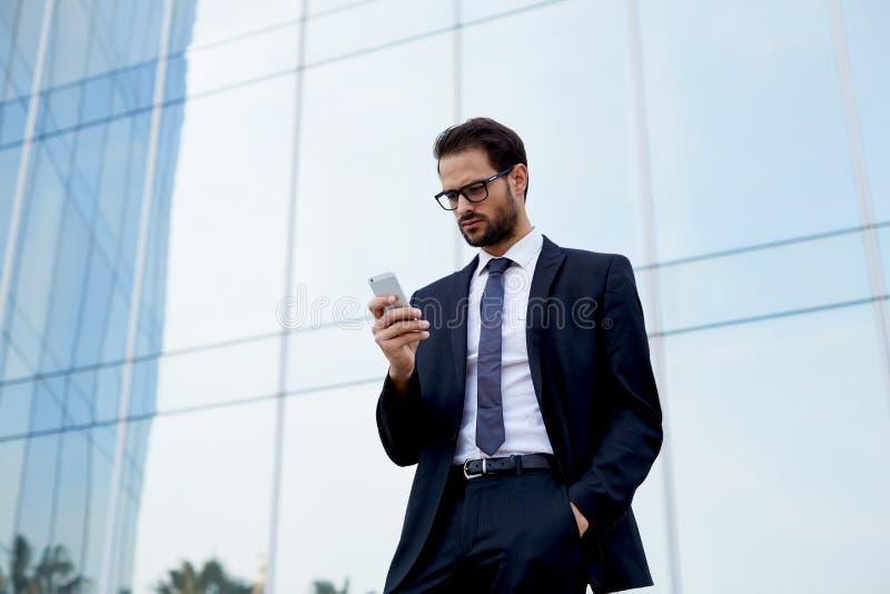 一家大公司的英俊的年轻经理是在办公室前面的一个电话 免版税库存照片