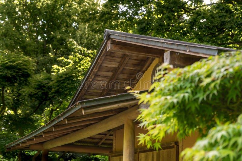 一家小日本茶馆的上半身在用密集的树盖的庭院里 库存照片
