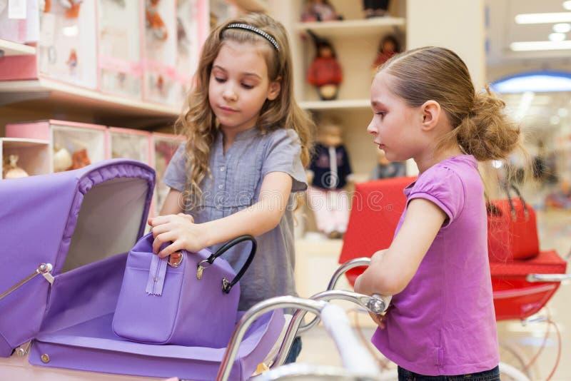 一家玩具店的两个女孩与玩偶购买了儿童车和提包 图库摄影