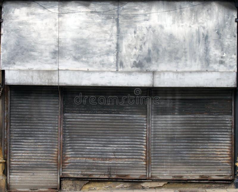 一家被放弃的商店的前面在一条街道上的有在商店前面和门的闭合的生锈的金属快门的 库存图片