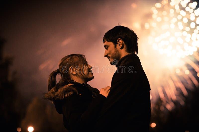一对亲吻的夫妇的剪影在巨大的烟花显示前面的 免版税图库摄影