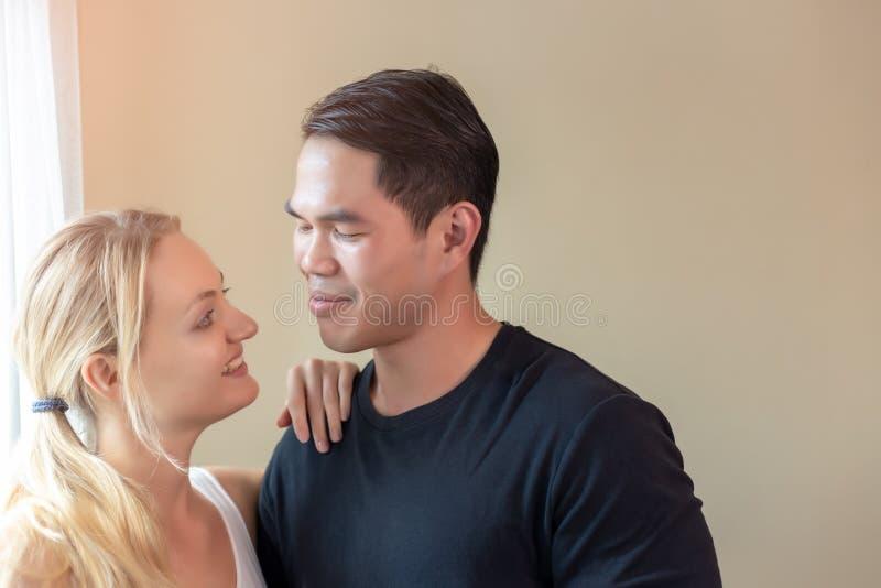 一对可爱的夫妻或情人,笑着看着彼此 帅气的亚洲小伙子和漂亮的白人女子 库存照片