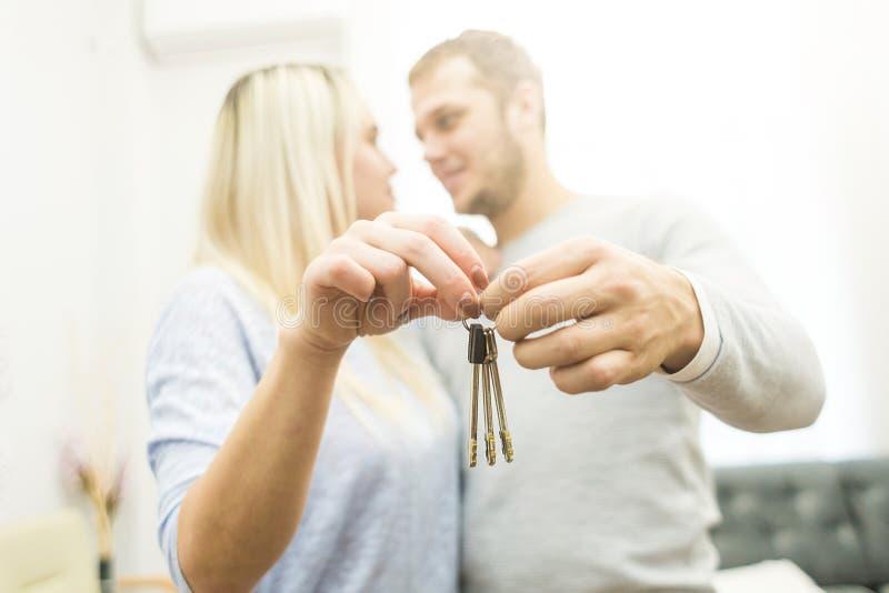 一对可爱的年轻夫妇在他们前面把握关键对他们新的公寓 免版税库存图片