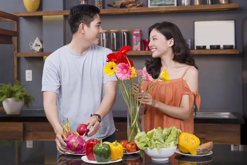一对夫妇在厨房里用很多水果和蔬菜 免版税库存图片